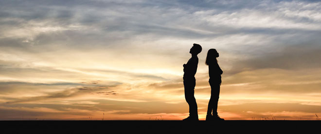 man and woman standing not facing each other, may be contemplating divorce